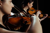 Fotografie young professional musicians playing classical music on violins on dark stage