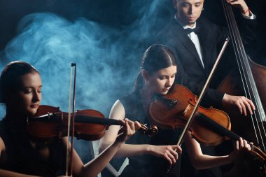 trio of musicians playing on violins and contrabass on dark stage with smoke
