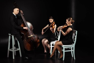 trio of professional musicians playing classical music on violins and contrabass on dark stage