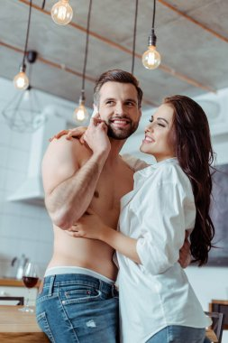 Happy woman hugging sexy shirtless boyfriend while man talking on smartphone in kitchen stock vector