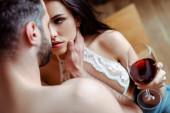Selektiver Fokus des Mannes berührt sexy junge unbekleidete Frau mit einem Glas Wein in der Küche