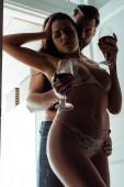 Fotografie sexy junge leidenschaftliche entkleidete Paar mit Rotwein umarmt nahe der Tür