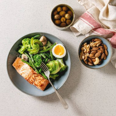Ketogenic low carb diet dinner grilled salmon, avocado, broccoli, green bean and soft boiled egg in ceramic bowl served with olives and nuts over grey spotted background. Flat lay, space stock vector