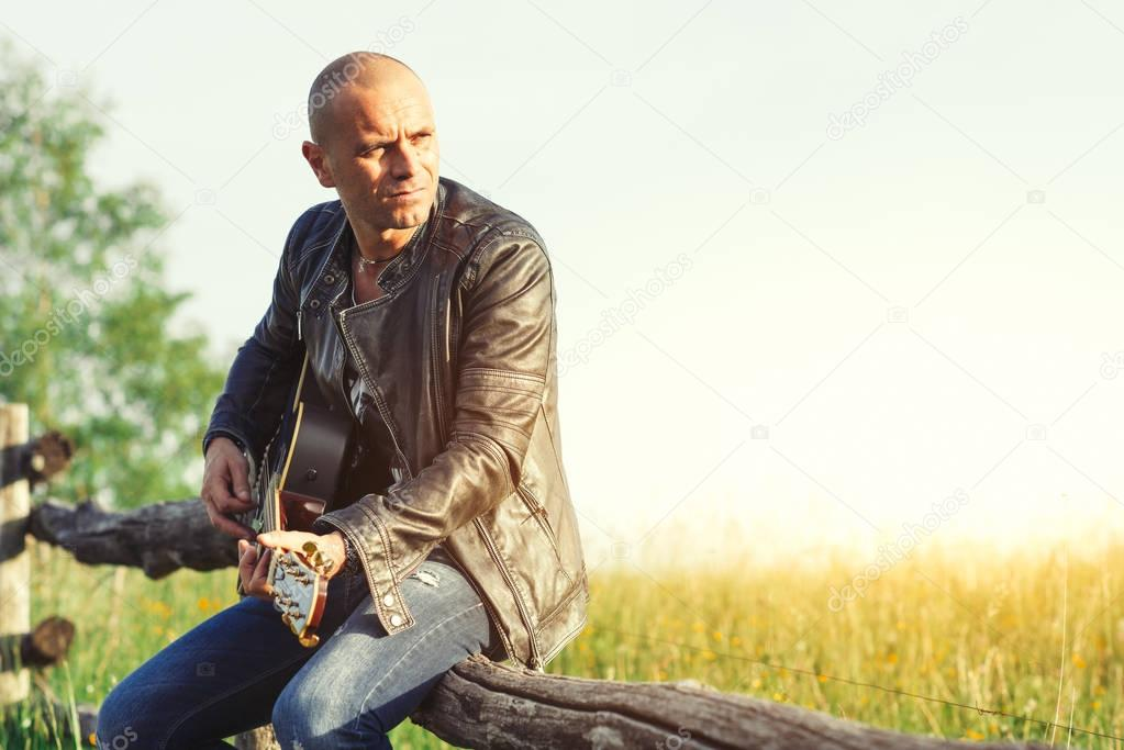 Singer with guitar on a fence in the meadow