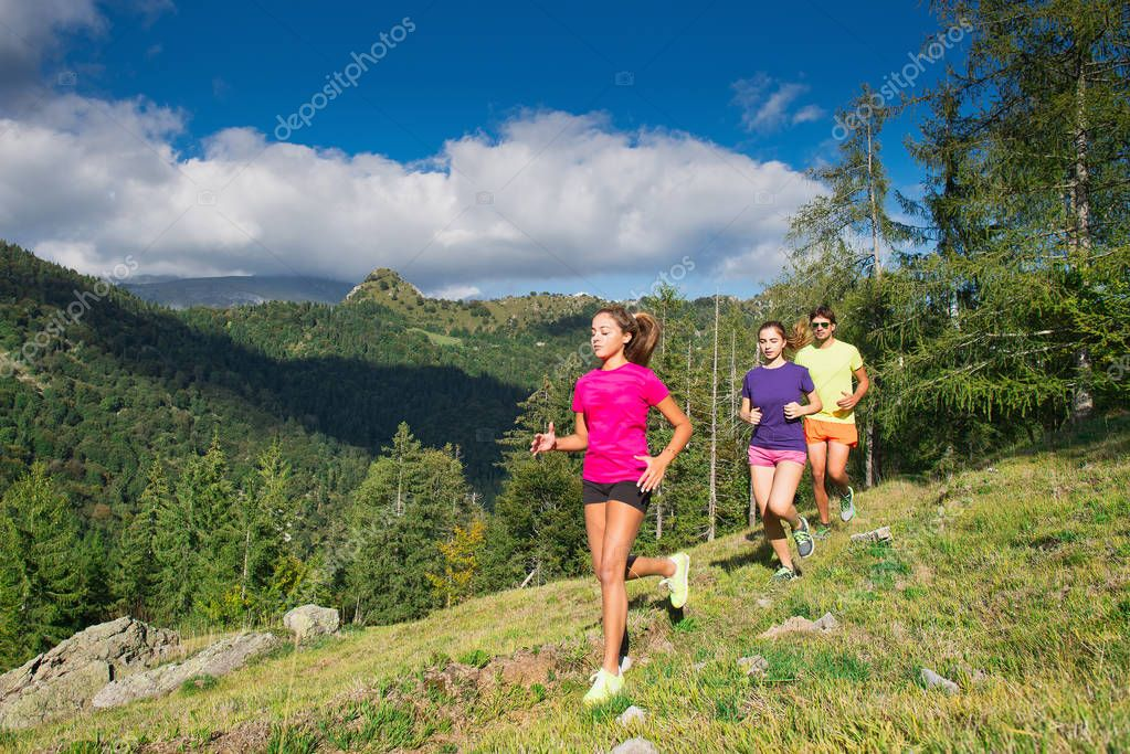 Two young sporty girls and a boy running together on the grass i