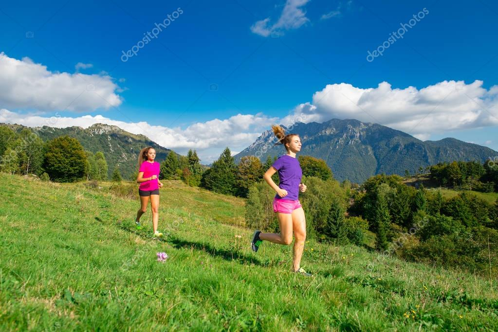 Two young sporty girls running together on the grass in a mounta