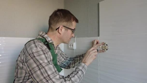 Elektrikář používá šroubovák k upevnění zásuvky na stěnu.