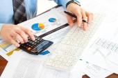 obchodní muž na pracovišti s pen, klávesnice, kalkulačky