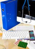 Fotografie Arzt-Arbeitsplatz mit Pillen und Tastatur mit Anamnese