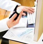 Fotografia medico che tiene la bottiglia di pillole in mano e si utilizza il computer per preparare prescrizione on-line