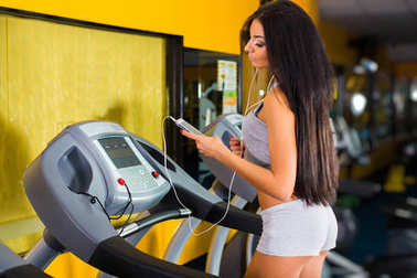 Smiling athletic woman training on a running machine with earphones in a fitness center