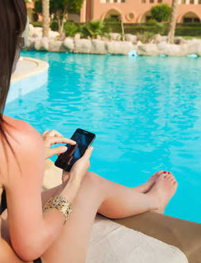 girl in a bathing suit lying on a sun lounger by the pool with a mobile phone with isolated screen