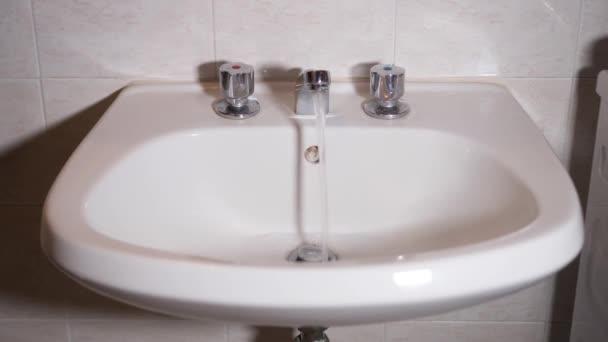 A fürdőszobai csap kinyílik és kiengedi a vizet.