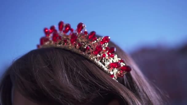 Diadem with red gems on the girls head