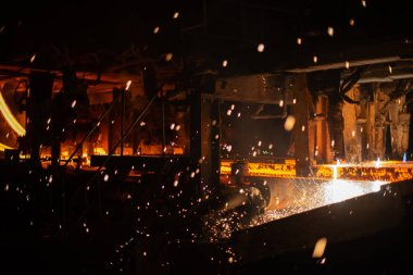 Hot red steel billets at torch cutting. Background of the blacksmith and metallurgical industry.
