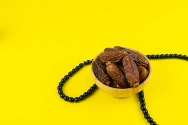 Ramadan Kareem Festival. Close up of dried dates fruit in bowl with rosary on yellow background. Copy space
