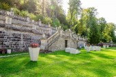 Fotografie Cantacuzino Palace courtyard with an old stone wall, garden furniture, freshly green cut grass and a tall forest on the background on a sunny summer day