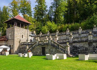 Cantacuzino Palace garden with exterior furniture and a guard tower on a sunny bright warm day