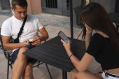Young people, man in white t-shirt and brunette girl in glasses sitting on the street terrace of cafe and playing with their phones