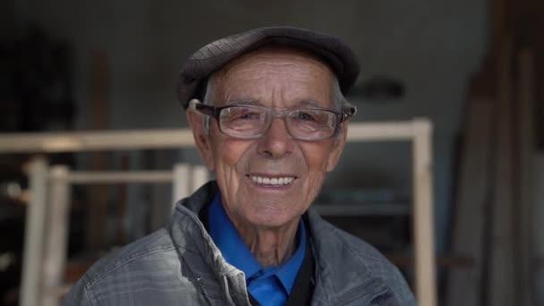 Nahaufnahme eines lächelnden alten Mannes mit blauen Augen, Brille, blauem Hemd, grauer Jacke und Hut, der in die Kamera schaut, inmitten seiner Tischlerei