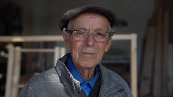 Nahaufnahme eines alten Zimmermanns mit blauen Augen in blauem Hemd, grauer Jacke und Hut, der in seine Werkstatt schaut