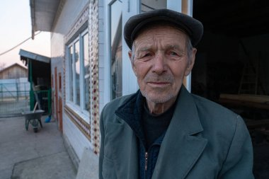 Waist up photo of old man in grey blazer and hat stands near his house