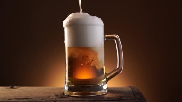 Fényes és friss sört öntenek egy nagy üvegpohárba.