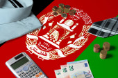 Fotografie Afghanistan flag on minimal money concept table. Coins and financial objects on flag surface. National economy theme.