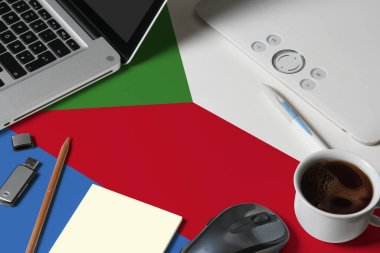 Comoros national flag on top view work space of creative designer with laptop, computer keyboard, usb drive, graphic tablet, coffee cup, mouse on wooden table.