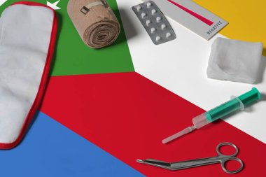 Comoros flag with first aid medical kit on wooden table background. National healthcare system concept, medical theme.