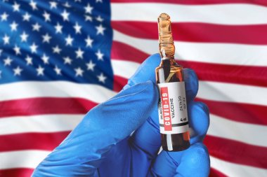 United States flag with Coronavirus Covid-19 concept. Doctor with blue protection medical gloves holds a vaccine bottle. coronavirus covid 19 vaccine research.
