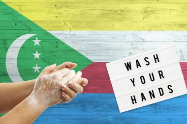 Comoros flag background on wooden surface. Minimal wash your hands board with minimal international hygiene concept hand detail.