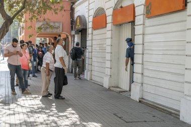 City: Santiago Country: Chile 26th March 2020 People waiting in Providencia streets to enter inside the banks and shops during the last hours before the curfew because of coronavirus disease COVID-19