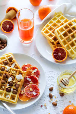 Healthy breakfast. Belgian waffles with nuts and Sicilian oranges on the white table