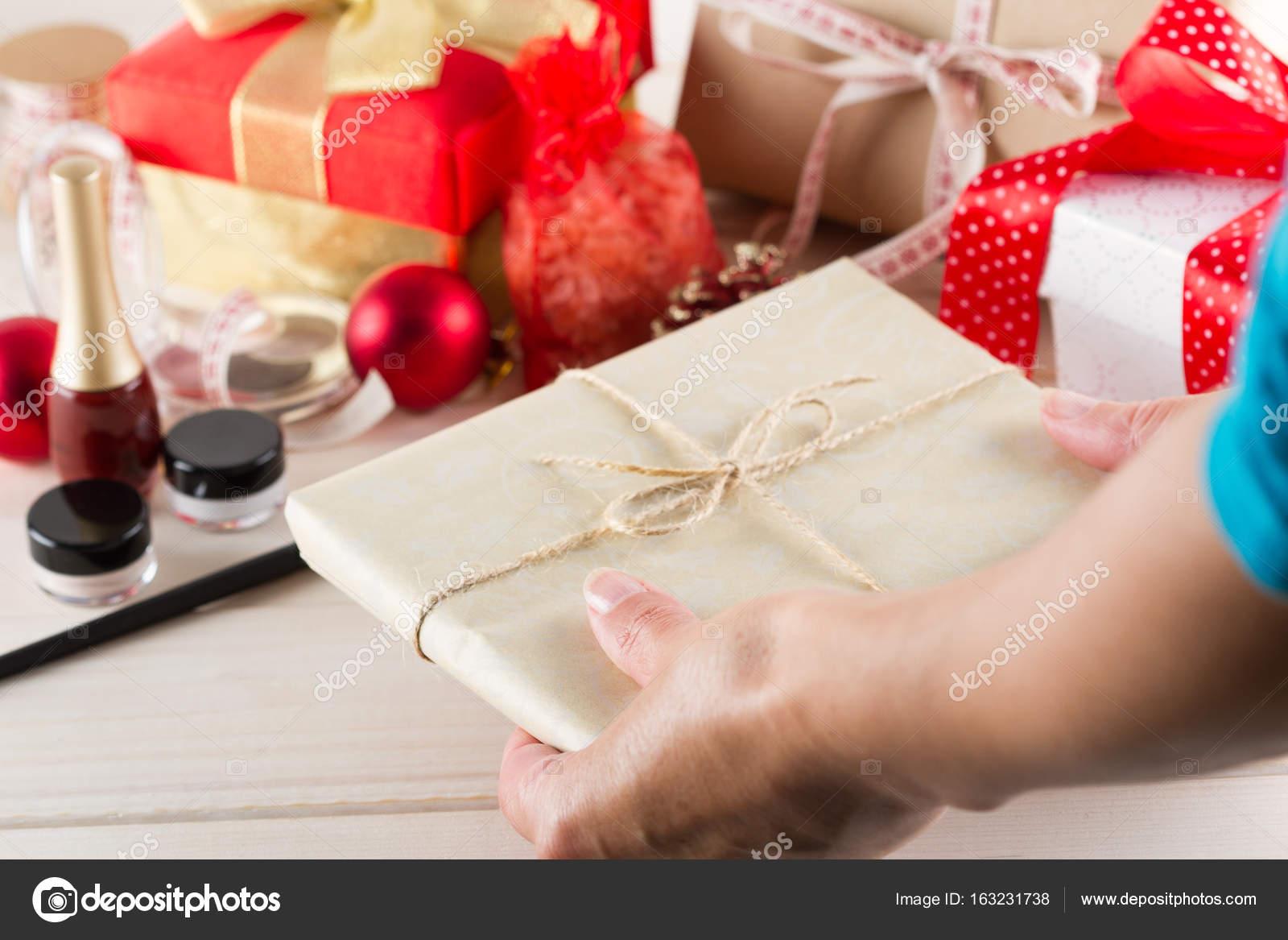 Frauenhänden sind in Weihnachtsgeschenke auf weißem hintergrund ...