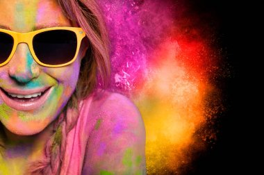 Happy young woman wearing trendy yellow sunglasses enjoying celebrating Holi fest covered in vibrant colorful powder pink, magenta and yellow with bursts of color behind over black with copy space stock vector