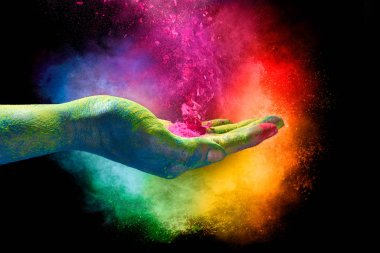 Magical rainbow colored powder exploding from the palm of a cupped hand creating a vibrant cloud of dust in the colors of the spectrum over a black background. Holi festival concep stock vector