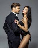 Fotografie Gut aussehender Mann im schwarzen Anzug berühren sexy Frau in Dessous