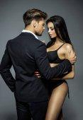 Pohledný muž v černém obleku dotýká sexy žena ve spodním prádle