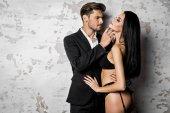 Jóképű férfi fehérnemű szexi nő megérintette fekete öltöny