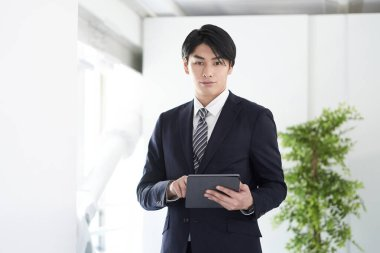 A Japanese businessman looking at the camera with a serious expression.