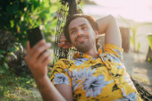 A young man lies in a hammock on a sunny beach with a phone.