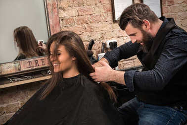 Hairdresser during work with woman