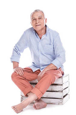 Elderly man sitting on wooden box