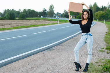 Young woman hitchhiker on road