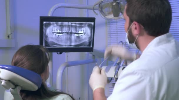 Dentist shows a patient x-ray picture of his teeth during treatment