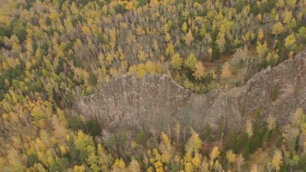 Vzdušný pohled na skálu mezi podzimním lesem.