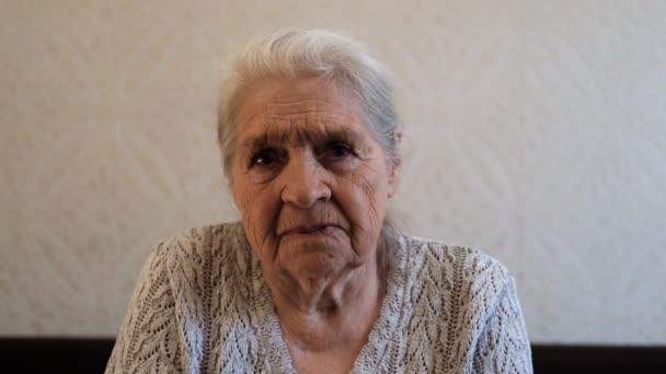 Egy idős, ősz hajú, komoly nő portréja.