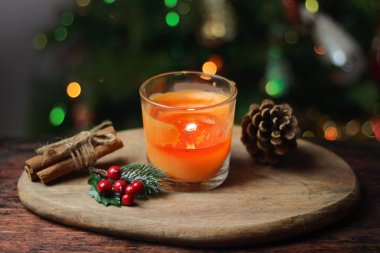 Beautiful Christmas orange mandarin candle on a wooden stand with sticks of whole cinnamon, sprig of mistletoe and a Christmas tree decorated with toys. Christmas New year evening mood, greeting card