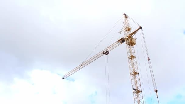 Baukran auf Baustelle Organisation der Arbeiten auf einer Baustelle mit einem Kran. Mechanismus zum Heben von Gütern auf einer Baustelle